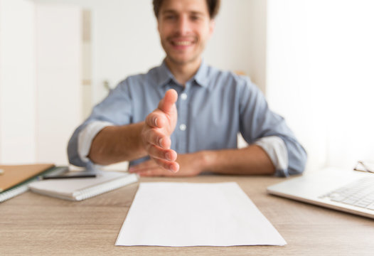 Millennial Guy Stretching Hand For Greeting At Workplace