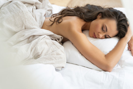 Beautiful young woman sleeping on her stomach in bed
