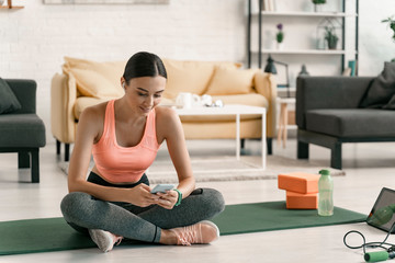 Cheerful woman exercising with gadget at home stock photo