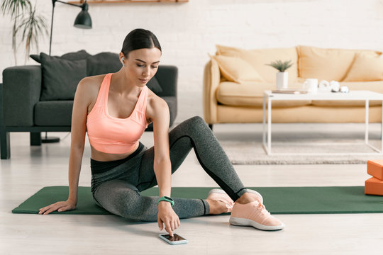 Woman using smartphone during home workout stock photo