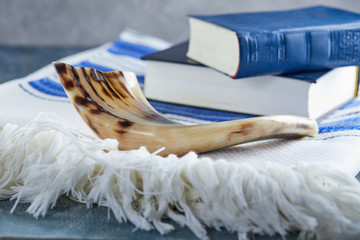 Rosh hashanah - jewish New Year holiday concept. Traditional symbols: Shofar - horn, tallite and Torah on a gray background