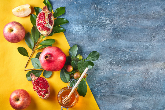 Rosh hashanah - jewish New Year holiday concept. Traditional symbols: Honey jar and fresh apples with pomegranate and shofar -horn on orange-blue background. Copy space for text.