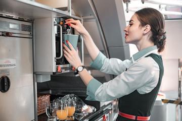Charming Caucasian female flight attendant making coffee on board