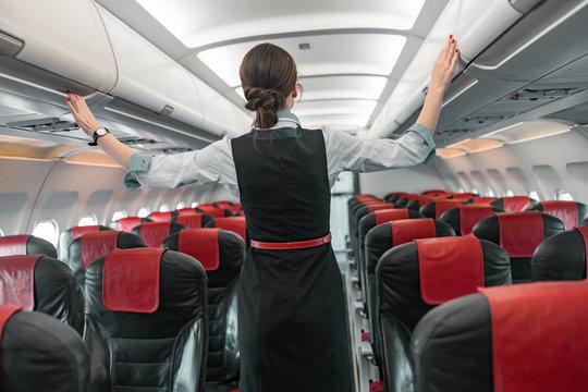 Caucasian adult stewardess is on duty on board