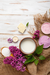 Spa and bath cosmetics with lilac flowers. Bath salt, soap, cream, oil, serum and towel rolls on...