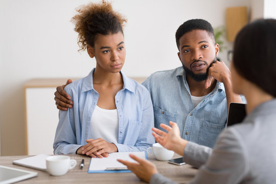 Serious Black Couple Listening To Financial Advisor During Investment Consultation