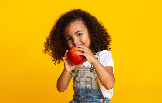 Yummy. Little afro girl eating red apple