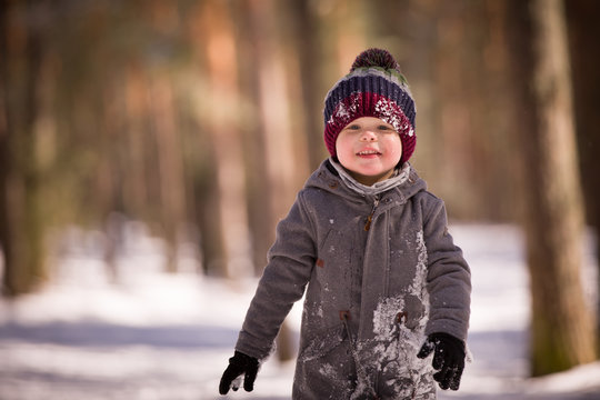 Handsome smiling little boy wearing a stylish coat and knitted hat, playing in the park. Snowy winter. A child playing with snow and runs in a snowy forest. Family winter holiday with a child