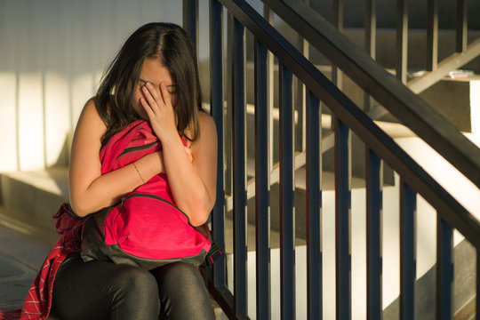Young beautiful depressed Asian Chinese college student sitting on campus staircase victim of abuse feeling scared and lonely being harassed and bullied