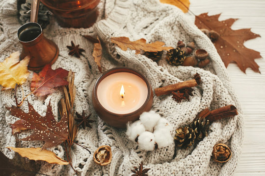 Hygge lifestyle. Candle with berries, fall leaves, anise,herbs, acorns, nuts , cinnamon, cotton on white knitted sweater. Autumn mood. Hello autumn, cozy inspirational image