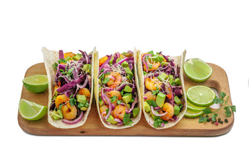 Tex-Mex fast food made of shrimps, avocado and onion. Tasty tacos on a wooden board. Top view, studio shot, isolated on white background.