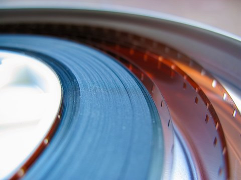 Roll of developed Super 16mm Film Negative on a Bobby in a can. 16mm Film is a popular and economical gauge of film stock