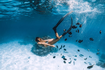 Woman freediver glides with fins over sandy sea with fishes in Hawaii Wall mural