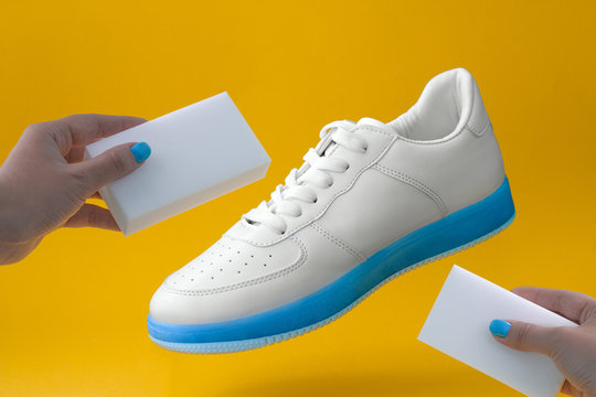 trendy white sneakers with blue sole  and female hands with sponges  on a yellow background , shoes care concept