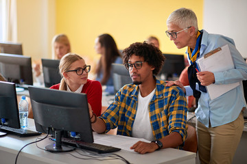 Woman lecturer in computer class assisting student.