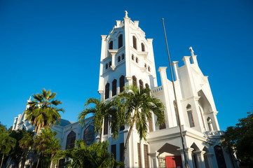 Bright scenic view of St. Paul's Episcopal church (built 1919) in simple white concrete with palm trees in Key West, Florida, USA
