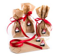 Weihnachtsgeschenke isoliert mit Wichtel Anhänger: Tüte mit roter Schleife und Wichtel Santa Anhänger