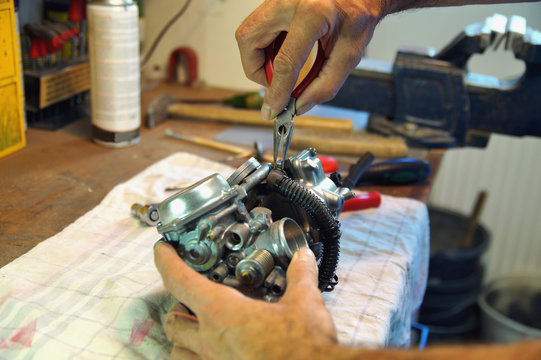 motorcycle carburetor. Automotive Carburetor Repair. Male Using A tong To Rebuild A Carburetor On A Workbench. Mechanic man checking carburetor of motorcycle. Repair. Maintenance and fixing concept.