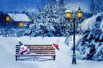 Santa hat and New Year's soft toy on a bench in the winter forest against the background of a village house and lantern. Christmas art card. Winter magical country.