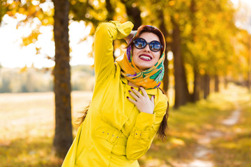 Stylish beautiful lady in a yellow raincoat and head scarf, sunglasses, autumn walk in the woods, fashion trend of the season