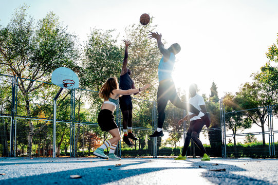 African friends and a girl playing on basketball court