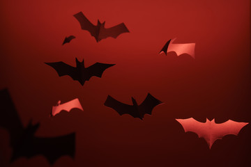 Image of gray paper bats on blank red background.