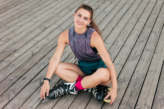 Young happy woman roller skater sitting wooden boards outdoors. Sport lifestyle