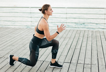 Young sport woman lunges on the beach terrace