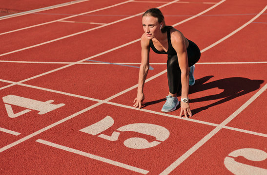 Young runner woman in sportwear getting ready to run sprint at low start on stadium track with red coated at bright sunny day