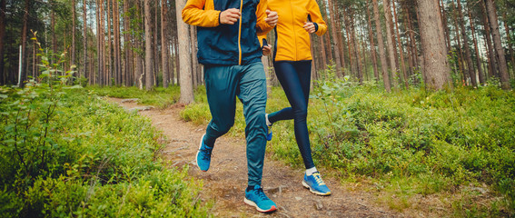 Couple running forest trail. Fitness fast movement stretching training park