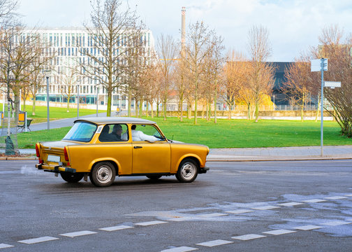 Yellow old car on road in Berlin Mitte