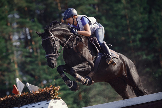 close portrait of attractive rider woman jumping over obstacle on black horse during eventing cross country competition in summer