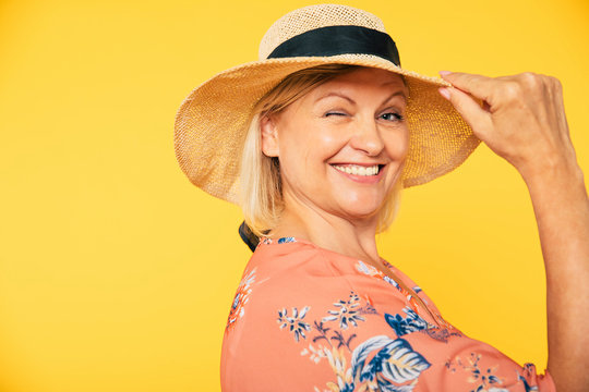 Beautiful smiling and happy cute senior woman in colorful clothes is posing on yellow background. Holidays and vacation. Summer mood