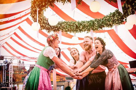 Gruppe von Freunden mit Bier auf der Bierbank tanzt auf der Dult Oktoberfest Regensburg München