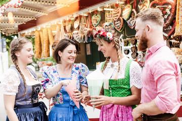 Fototapete - Gruppe mit Trachten auf Volkfest teilt sich eine Tüte Süßes vor Laden