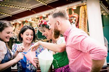 Fototapete - Gruppe von Freunden in Tracht auf der Dult, Oktoberfest teilt sich eine Tüte Süßes