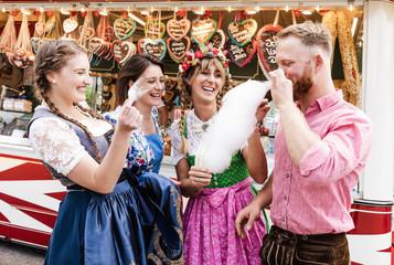 Fototapete - Gruppe nascht Zuckerwatte auf dem Volkfest im Dirndl Trachten Dult