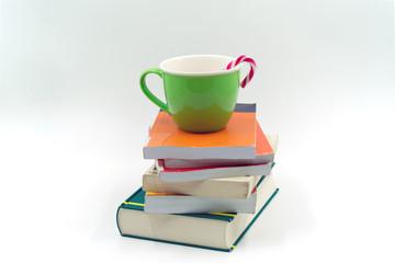grüne Tasse mit Zuckerstange auf einem Bücherstapel.