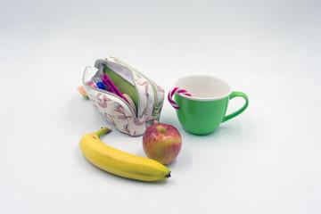 Schuletui mit gesundem Frühstück und grüner Tasse mit Zuckerstange