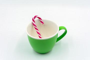 grüne Kaffeetasse mit Zuckerstange.