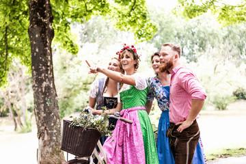 Fototapete - Gruppe von junge Freunden in Trachten und Dirndl läuft zum Volksfest