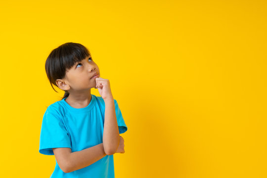 Portrait of young girl thinking and get idea, Thai student kid in soft blue shirt standing  and guess isolated on yellow background
