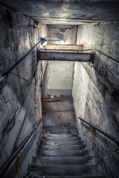 Scary stairwell leading down to a dark tunnel