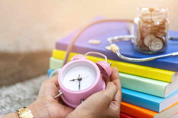 close up a vintage pink alarm clock in the hands of a woman.