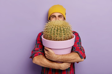 Photo sur Plexiglas Cactus Photo of happy young male flower grower embraces big pot with prickly cactus, wears stylish hat and checkered shirt, glad to receive house plant as gift, isolated on purple wall. Gardening concept