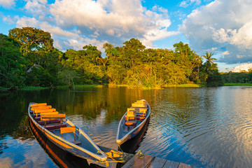 Poster Brésil Two traditional wooden canoes at sunset in the Amazon River Basin with the tropical rainforest in the background inside the Yasuni National Park, Ecuador, South America.