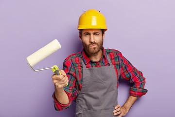 Serious man painter holds painting roller, does redecoration at home, paints walls, wears protective helmet and apron, poses indoor, busy with repairing and renovation, isolated on purple background.
