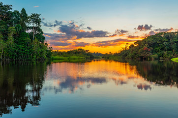 Reflection of a sunset by a lagoon inside the Amazon Rainforest Basin. The Amazon river basin comprises the countries of Brazil, Bolivia, Colombia, Ecuador, Guyana, Suriname, Peru and Venezuela.  Fototapete