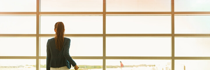 Airport travel businesswoman on business trip vacation waiting for flight looking out the window at tarmac. Banner panoramic header with copy space on windows background. People traveling lifestyle.