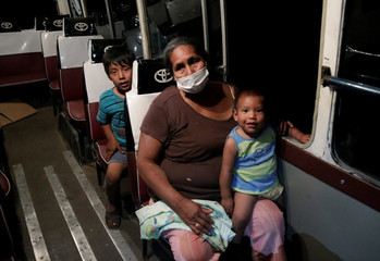 A woman and children are seen in a bus before evacuation  in San Lorenzo Community an area where wildfires have destroyed hectares of forest, near Robore